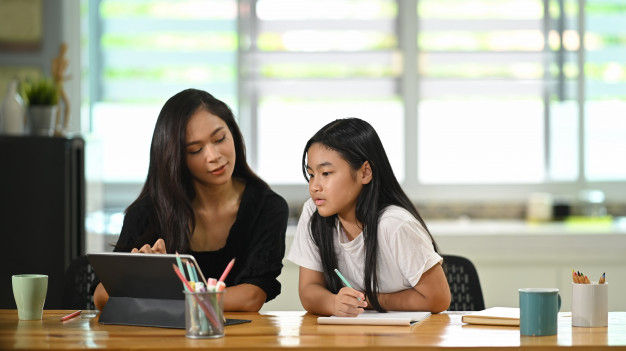 young-mother-sits-doing-homework-together-with-her-daughter-wooden-student-desk